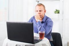 Uomo d'affari che lavora nell'ufficio, sedentesi ad una tavola che tiene tazza e che guarda diritto Immagini Stock