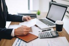 Uomo d'affari che lavora nuovo progetto sul computer portatile con il documento di rapporto ed analizzare, calcolando i dati fina immagini stock