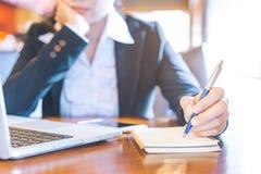 Uomo d'affari che lavora in un computer portatile e che scrive una nota con Fotografia Stock Libera da Diritti
