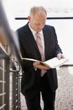 Uomo d'affari che legge con attenzione le scale del paperworkon Fotografie Stock