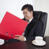 Uomo d'affari che legge il suo lavoro immagini stock