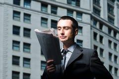 Uomo d'affari che legge un giornale immagini stock