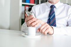 Uomo d'affari che manda un sms con lo smartphone e che beve un caffè Fotografia Stock