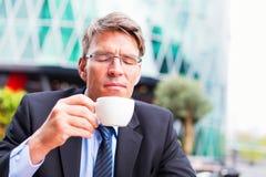 Uomo d'affari che mangia caffè Fotografia Stock
