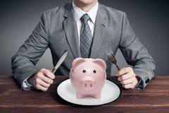 Uomo d'affari che mangia porcellino salvadanaio Concetto di affari fotografia stock libera da diritti
