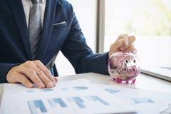 Uomo d'affari che mette le monete nel porcellino salvadanaio e che per mezzo del calcolatore t Immagini Stock Libere da Diritti