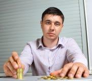 Uomo d'affari che mette le monete nelle colonne Fotografie Stock Libere da Diritti
