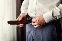 Uomo d'affari che mette su una cinghia L'uomo mette sopra la cinghia marrone Fuoco sopra Fotografie Stock
