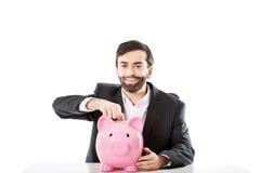 Uomo d'affari che mette una moneta al porcellino salvadanaio Fotografie Stock