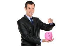 Uomo d'affari che mette una moneta in una banca piggy Immagini Stock