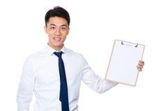Uomo d'affari che mostra con la lavagna per appunti ed il Libro Bianco fotografia stock