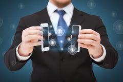 Uomo d'affari che mostra gli smartphones con gli schermi in bianco Fotografie Stock Libere da Diritti