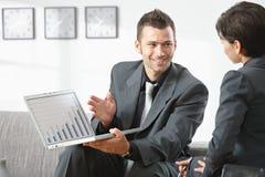 Uomo d'affari che mostra grapth sul calcolatore Fotografie Stock