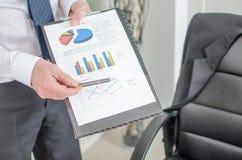 Uomo d'affari che mostra i grafici finanziari Immagini Stock