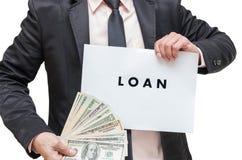 Uomo d'affari che mostra il segno di PRESTITO con i soldi del dollaro americano su bianco Fotografia Stock Libera da Diritti