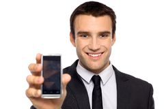 Uomo d'affari che mostra il suo telefono mobile Fotografia Stock Libera da Diritti