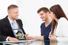 Uomo d'affari che mostra l'immagine della casa alle coppie sul computer portatile fotografia stock