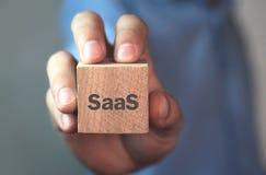 Uomo d'affari che mostra parola di SaaS sul cubo di legno fotografia stock libera da diritti
