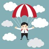 Uomo d'affari che mostra pollice su flyimg con il paracadute nel cielo Fotografie Stock