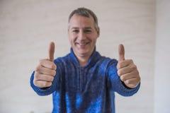 Uomo d'affari che mostra segno GIUSTO con il suo pollice in su Fuoco selettivo immagine stock