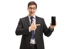 Uomo d'affari che mostra un telefono ed indicare Fotografie Stock