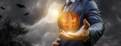 Uomo d'affari che mostra una zucca nel Halloween fotografia stock libera da diritti
