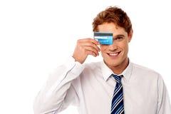 Uomo d'affari che nasconde il suo occhio con la carta di credito Immagini Stock