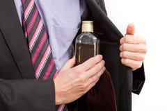 Uomo d'affari che nasconde un alcool Fotografia Stock Libera da Diritti