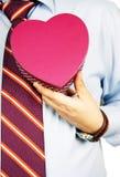 Uomo d'affari che nasconde un regalo Fotografia Stock Libera da Diritti
