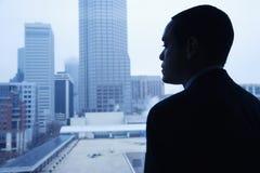 Uomo d'affari che osserva attraverso una finestra Fotografia Stock Libera da Diritti