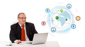 Uomo d'affari che osserva computer portatile con il globo Fotografia Stock