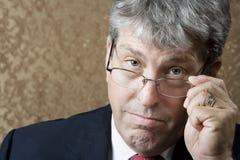 Uomo d'affari che osserva sopra i suoi vetri Fotografie Stock Libere da Diritti