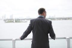 Uomo d'affari che osserva sopra il balcone Immagini Stock