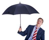 Uomo d'affari che osserva in su da sotto l'ombrello Immagine Stock