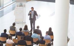 Uomo d'affari che parla alla conferenza mentre tenendo compressa digitale e microfono al seminario di affari fotografie stock libere da diritti