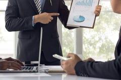 Uomo d'affari che parla con i colleghi circa finanza e successo di Fotografia Stock
