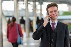 Uomo d'affari che parla sul telefono cellulare mentre pensando sul treno immediatamente immagine stock libera da diritti