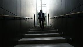 Uomo d'affari che parla sul telefono cellulare nell'ingresso dell'ufficio archivi video