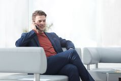 Uomo d'affari che parla sul telefono cellulare che si siede in una sedia Immagine Stock Libera da Diritti