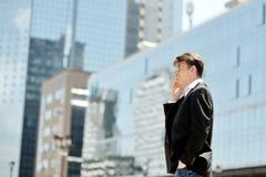 Uomo d'affari che parla sul telefono cellulare sulle costruzioni corporative dell'ufficio moderno del fondo Fotografie Stock Libere da Diritti