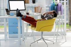 Uomo d'affari che parla sul telefono della linea terrestre mentre sedendosi sulla sedia con i piedi su Fotografia Stock