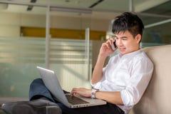Uomo d'affari che parla sul telefono e che lavora al computer portatile Fotografie Stock
