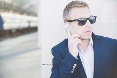 Uomo d'affari che parla sul telefono e che tiene un giornale Fotografia Stock