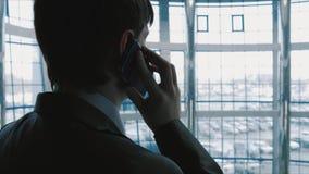 Uomo d'affari che parla sul telefono nell'elevatore che va giù video d archivio