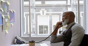 Uomo d'affari che parla sulla linea terrestre allo scrittorio 4k archivi video
