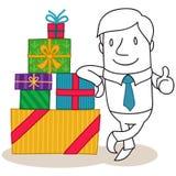 Uomo d'affari che pende contro la pila di contenitori di regalo Fotografia Stock Libera da Diritti