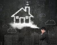 Uomo d'affari che pensa alla nuvola di forma della casa con la parete di scarabocchi Fotografia Stock Libera da Diritti