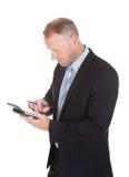 Uomo d'affari che per mezzo del calcolatore Immagini Stock Libere da Diritti