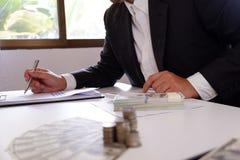 Uomo d'affari che per mezzo del calcolatore con soldi e la pila di monete sullo scrittorio fotografia stock libera da diritti