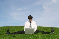 Uomo d'affari che per mezzo del computer portatile Fotografia Stock